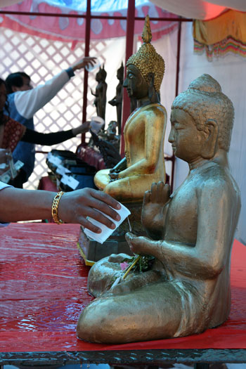 water pouring on Buddha images